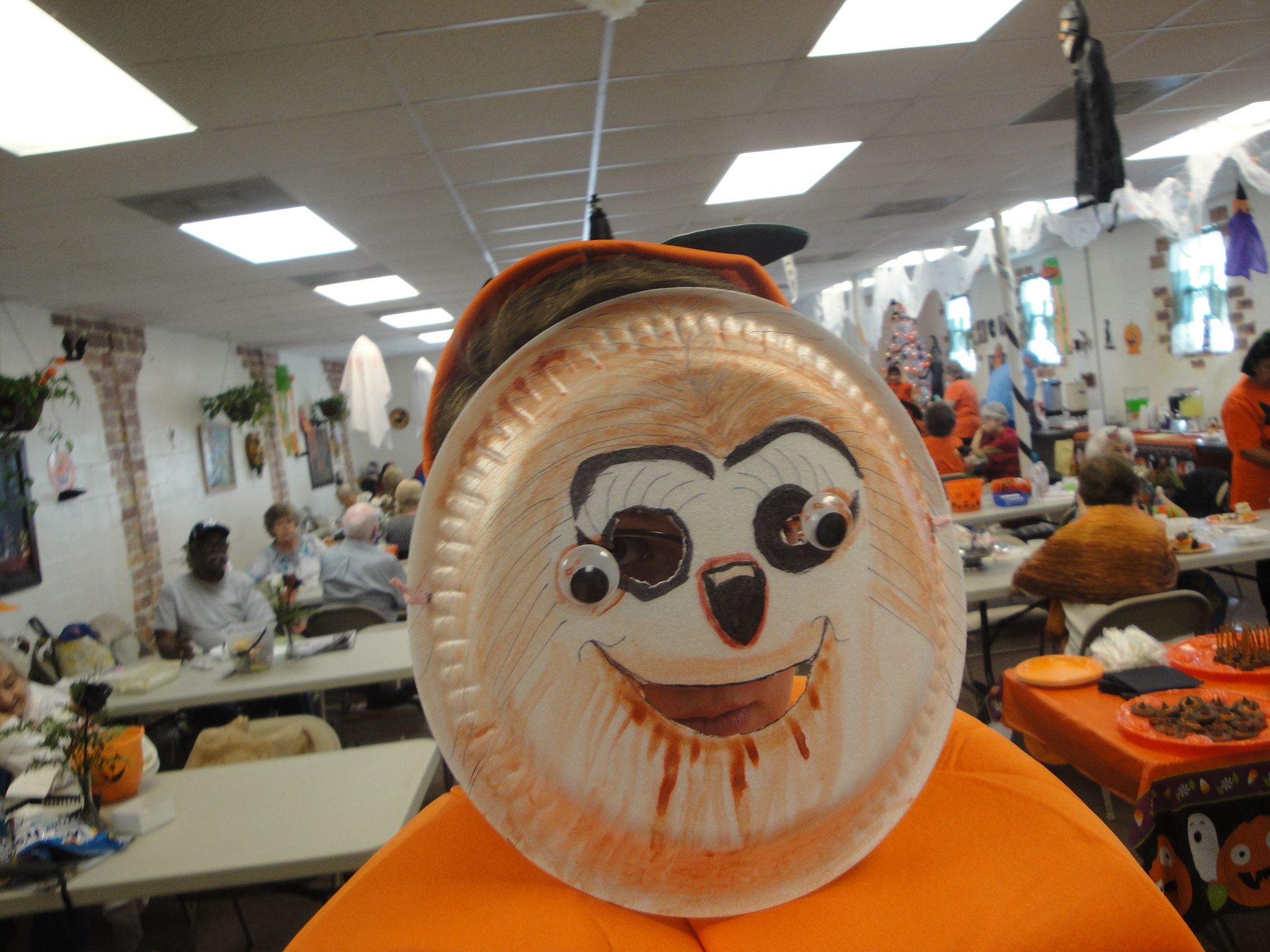 Halloween participant in a paper plate homemade mask and an orange shirt